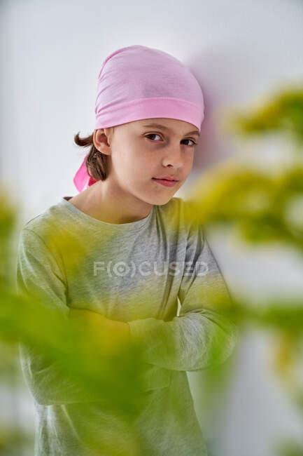 Niño enfocado con diagnóstico de cáncer usando bandana rosa y mirando a la cámara mientras sostiene el jarrón con flores y de pie en la pared - foto de stock