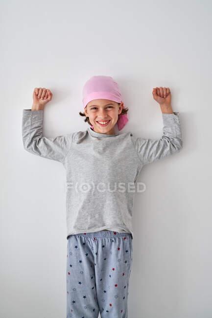 Храбрый маленький ребенок с диагнозом рак, смотрящий в камеру и кричащий, поднимая кулаки на сером фоне — стоковое фото