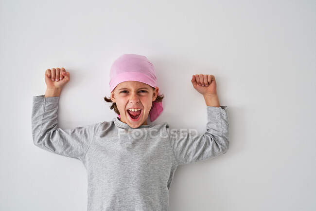 Brave small child with cancer diagnosis looking at camera and screaming while raising fists up on gray background — Stock Photo