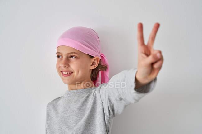 Un valiente niño pequeño con diagnóstico de cáncer mirando hacia otro lado haciendo un gesto de victoria con los dedos sobre un fondo gris - foto de stock