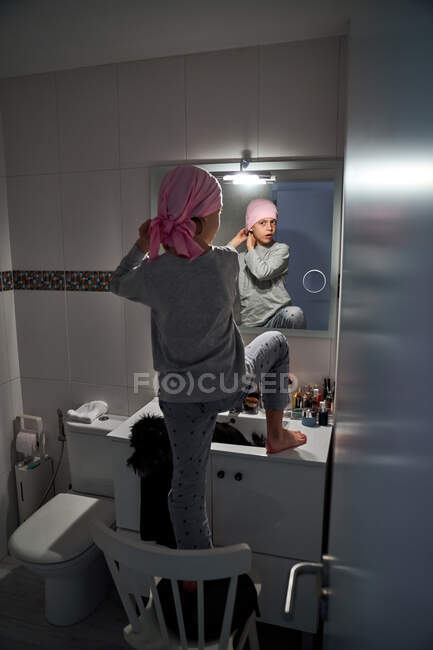 Back view of sick little child putting on pink bandana in front of mirror in bathroom — Stock Photo