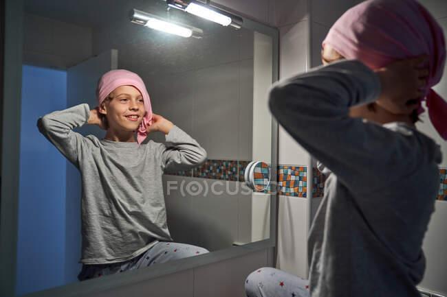 Vista trasera de un niño enfermo poniéndose pañuelo rosa delante del espejo en el baño - foto de stock