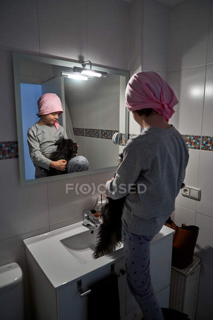 Back view of sick little child with pink bandana in front of mirror in bathroom holding a little cute dog — Stock Photo
