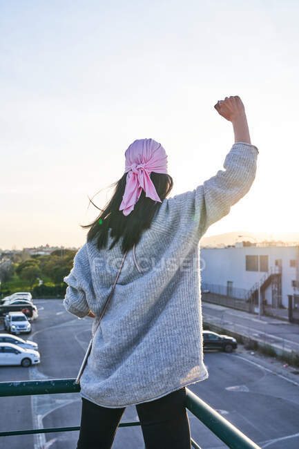 Back view of woman in pink bandana raising hand up and contemplating sundown while standing on roof of building in city — Stock Photo