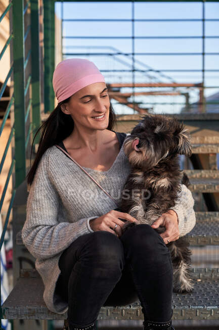 Happy young female in pink bandana caressing small breed dog while sitting on staircase in street — Stock Photo