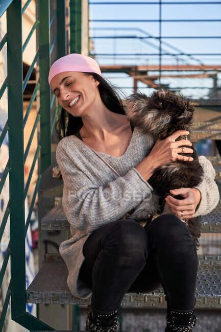 Feliz joven hembra en bandana rosa acariciando perro de raza pequeña mientras está sentado en la escalera en la calle - foto de stock