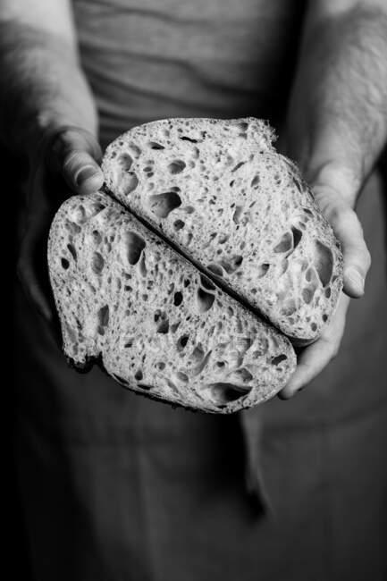 Пекар - самець у фартусі, який тримає наполовину шматок свіжого здорового ремісничого хліба. — стокове фото