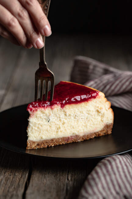 Crop female with fork eating delicious homemade cheesecake with red berry jam served on black plate on wooden table — Stock Photo