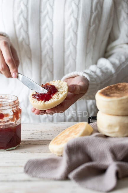 Closeup of crop person spreading yummy red berry jam on cut fresh homemade bun — Stock Photo