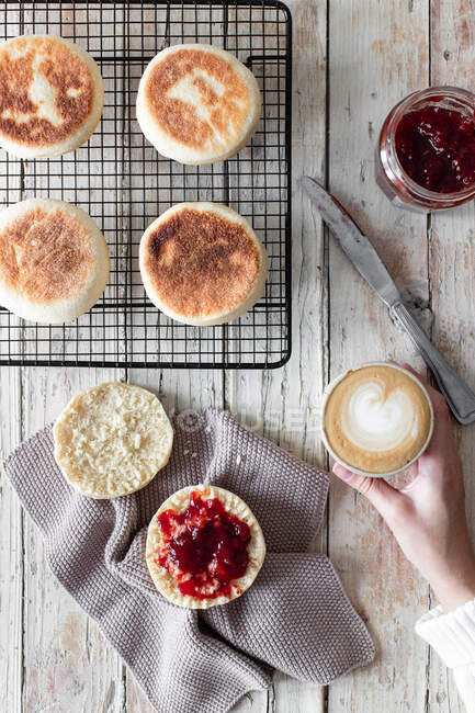 From above of crop female having breakfast at wooden table with cup of cappuccino and fresh homemade buns with berry jam — Stock Photo