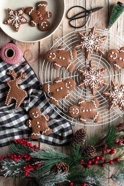 Vue de dessus du pain d'épice maison traditionnel avec glaçage placé sur une table en bois avec branche d'arbre décorative préparée pour la célébration de Noël — Photo de stock