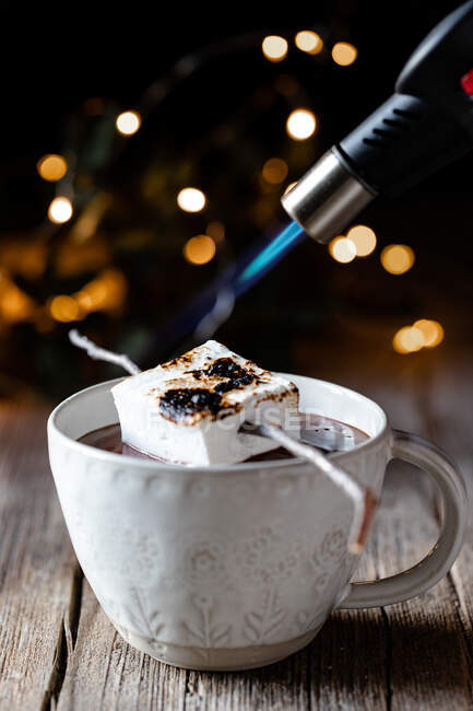 Anonymous person with kitchen burner roasting marshmallow placed on stick over elegant cup of hot chocolate on wooden table with sparkles in dark background — Stock Photo