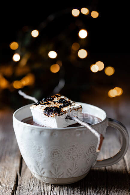 Roasted marshmallow placed on stick over elegant cup of hot chocolate on wooden table with sparkles in dark background — Stock Photo