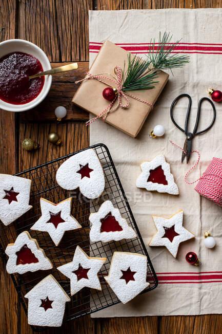 Vue de dessus des biscuits maison savoureux de différentes formes avec de la confiture de baies rouges et de la poudre de sucre blanc placés sur une table en bois avec des ustensiles et des éléments décoratifs pour la célébration de Noël — Photo de stock