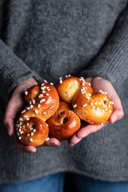 Crop female in cozy gray sweater and jeans holding traditional fresh baked saffron buns with raisin and sprinkles — Stock Photo