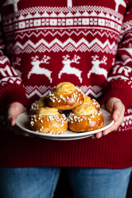Crop female in red christmas sweater and jeans holding plate with homemade pastry and demonstrating tasty fresh buns with white sprinkles — Stock Photo