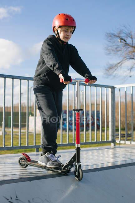 Adolescente activo en casco protector con patinete scooter de pie en rampa en skate park mientras se prepara para realizar truco en soleado día de primavera - foto de stock