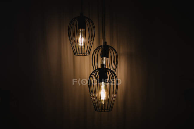 Hanging metal wired lanterns with glowing light bulbs illuminating dark room in Navarre, Spain — Stock Photo
