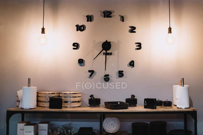 Стильные часы, установленные на светящейся белой стене над полкой с различными кухонными принадлежностями в кулинарной школе — стоковое фото
