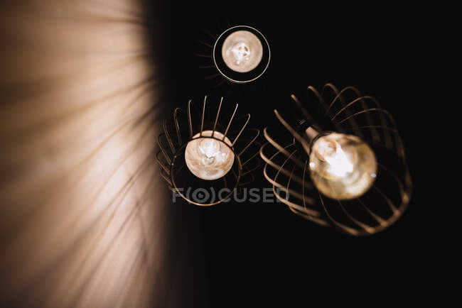 From below stylish lanterns with glowing light bulbs hanging from ceiling in dark room in Navarre, Spain — Stock Photo