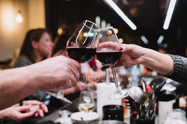 Pessoas irreconhecíveis batendo copos de vinho e propondo torradas enquanto jantam em oficina de culinária após aula em Navarra, Espanha — Fotografia de Stock