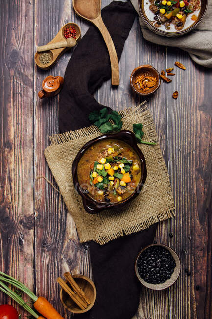 Top view of delicious spicy Mexican dish chili with meat made with hot pepper and minced meat and vegetables served on bowl on rustic wooden table with ingredients and utensils — стоковое фото