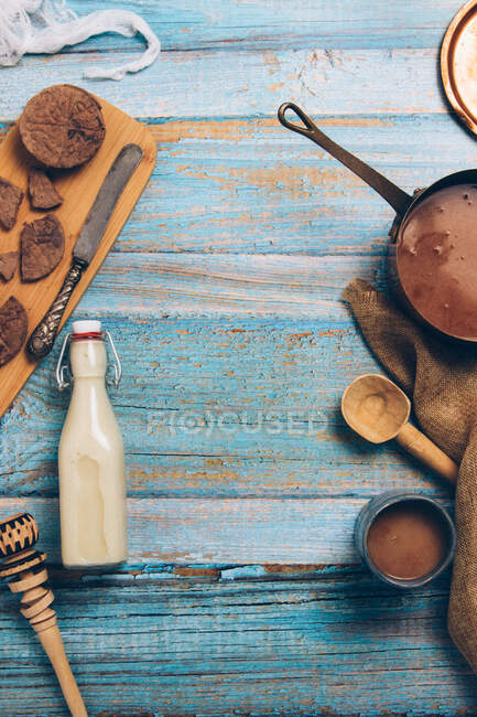 Top view composition with chunks of chocolate and bottle of milk placed with utensils for preparing traditional Mexican hot chocolate on shabby blue wooden table — Foto stock