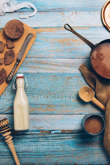 Zusammensetzung von oben mit Schokoladenstücken und einer Flasche Milch mit Utensilien zur Zubereitung traditioneller mexikanischer heißer Schokolade auf einem schäbigen blauen Holztisch — Stockfoto