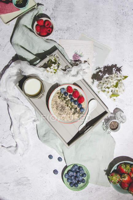 Vista dall'alto del delizioso porridge di avena sana con bacche fresche servite con tazza di latte su vassoio posto sulla superficie grigia con bacche e fiori — Foto stock