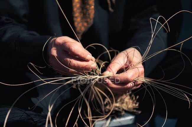Personne âgée méconnaissable faisant de l'osier à partir de matériaux naturels le jour ensoleillé — Photo de stock