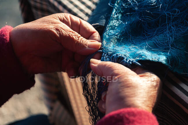 Unrecognizable senior tailor attaching fringe to cloth scarf while sitting at table — Stock Photo