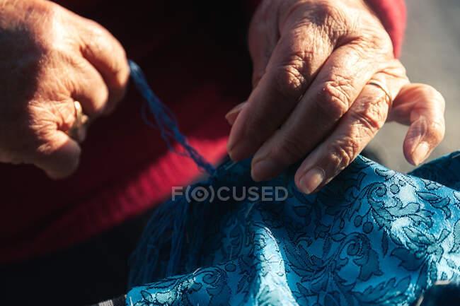 Crop elderly artisan making scarf — Stock Photo