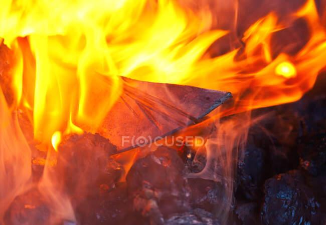 Knife blank on burning fire — Stock Photo