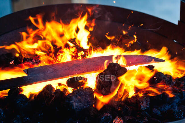 Metal blank for knife heating on blazing flame in hearth in forge — Stock Photo