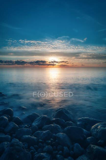 Pintoresca vista del cielo nublado del atardecer sobre el apacible agua de mar y la costa pedregosa de Cap des Falco en Ibiza, España - foto de stock
