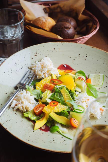 Верхний вид аппетитного красочного салата со свежими овощами и фруктами и измельченной курицей, подаваемой в миске — стоковое фото