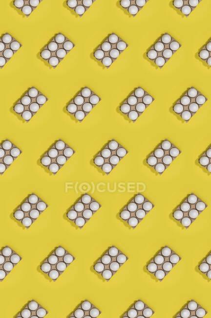 Яркий бесшовный пасхальный шаблон с белыми яйцами в коробках на желтом фоне — стоковое фото