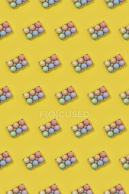 Bright seamless Easter template with white eggs in carton boxes on yellow background — Stock Photo