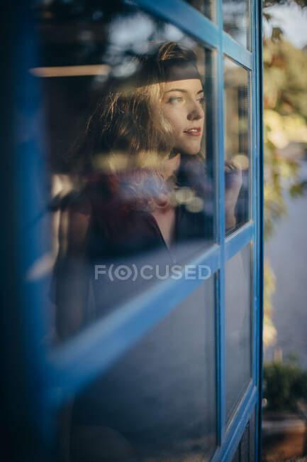 Giovane donna sorridente in body nero guardando altrove pensieroso e sorridente mentre in piedi vicino alla finestra a casa — Foto stock