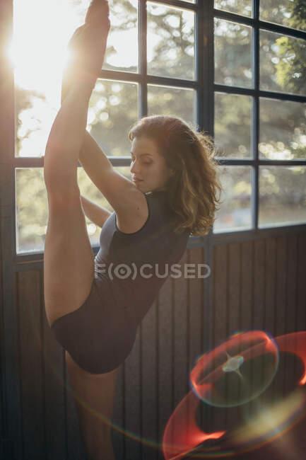 Seitenansicht einer jungen Tänzerin mit geschlossenen Augen im schwarzen Body, die am Fenster steht und das Bein streckt, während sie im Studio trainiert — Stockfoto