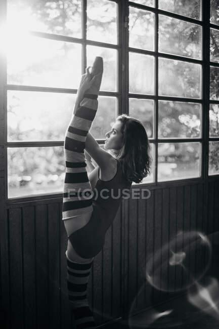 Seitenansicht einer jungen Tänzerin in schwarzem Body, die am Fenster steht und das Bein streckt, während sie im Studio trainiert — Stockfoto
