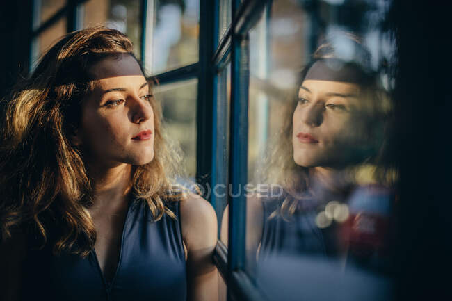 Giovane donna sorridente in body nero distogliendo lo sguardo pensieroso e sorridente mentre in piedi vicino alla finestra a casa — Foto stock