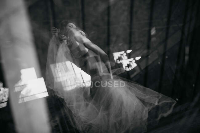 From below double exposure of young female dancer in ballet tutu standing in blinks of light in modern studio — Stock Photo
