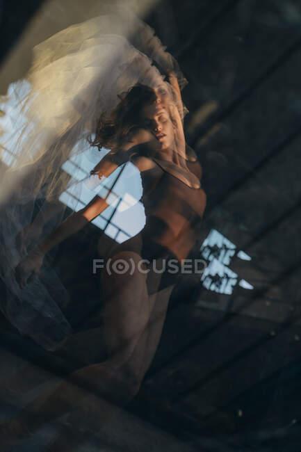 D'en bas double exposition de la jeune danseuse en tutu ballet debout en clignotements de lumière dans le studio moderne — Photo de stock