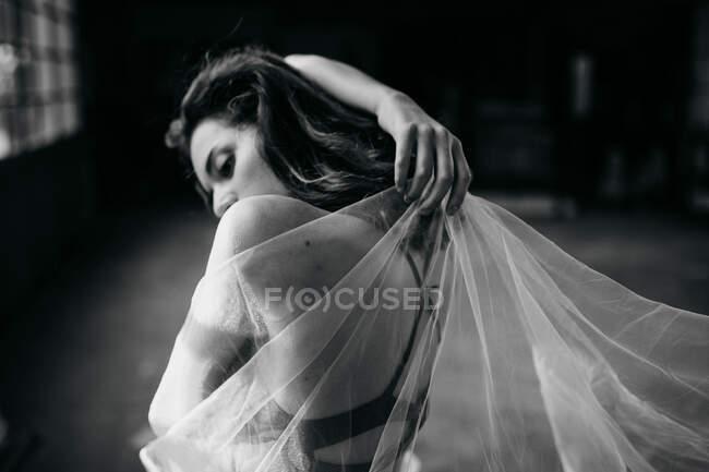 Молодая талантливая танцовщица, глядя вдаль, танцует с прозрачной вуалью, тренируясь в одиночестве в светлой студии. — стоковое фото