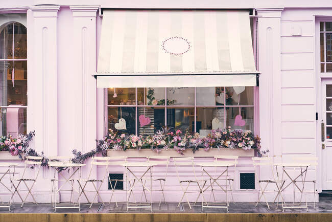 Facade of empty terrace of modern cafe with pink wall and window decorated with flowers and hearts on city street — Stock Photo