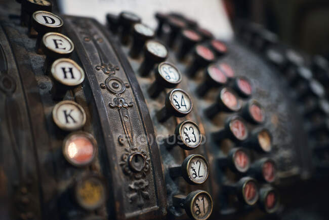 Closeup of antique vintage metal cash machine with keys with numbers and letters — Stock Photo