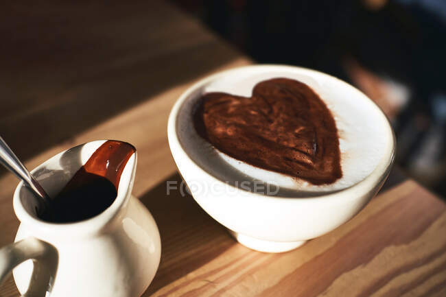 From above of cup of hot cappuccino with chocolate syrup in heart shape placed on wooden table in sunny room — Stock Photo
