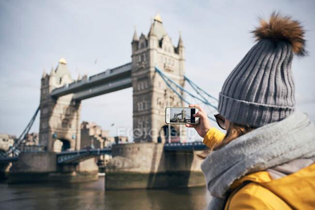 Vue arrière du voyageur féminin en vêtements chauds et chapeau prendre des photos de Tower bridge avec smartphone lors de visites touristiques à Londres par temps ensoleillé — Photo de stock