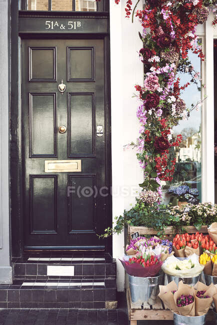 Wooden stall with bouquets of flowers located on city street near black door of residential building in city — Stock Photo